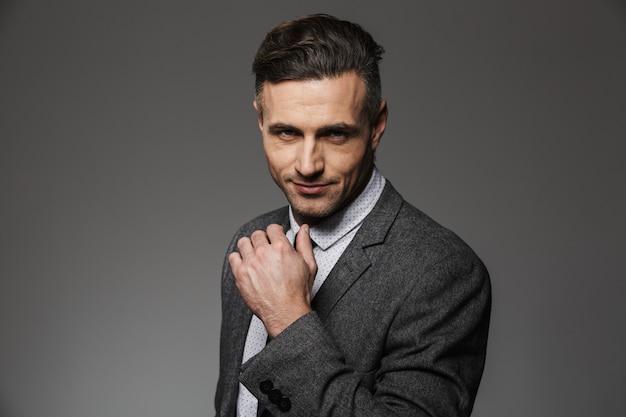 Foto primo piano di uomo d'affari che indossa abito formale con sguardo sicuro, isolato su muro grigio