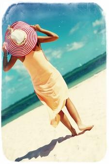 Foto retrò vintage di bella donna calda in cappellino colorato e abito camminando vicino oceano sulla spiaggia in una calda giornata estiva sulla sabbia bianca