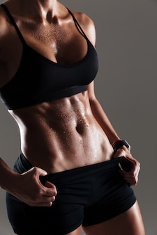 Foto ritagliata del fantastico corpo di giovane donna sportiva