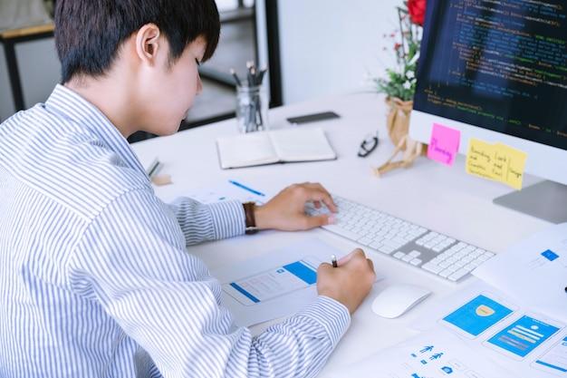 Foto ritagliata del progettista di applicazioni mobili che progetta layout di schermate wireframe mobili per la codifica o la programmazione di applicazioni mobili.