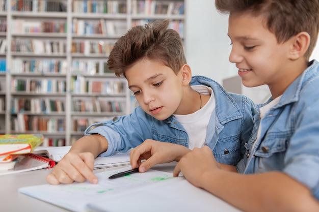 Foto ritagliata di due giovani fratelli gemelli che fanno un progetto scolastico insieme in biblioteca