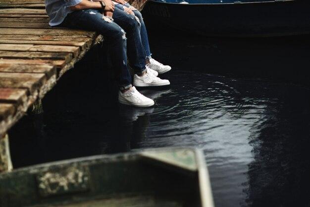 Foto ritagliata giovani innamorati coppia sposata, marito e moglie, tenuta di mani sedersi su un ponte di legno vicino al lago. la metà inferiore. posto per il testo.