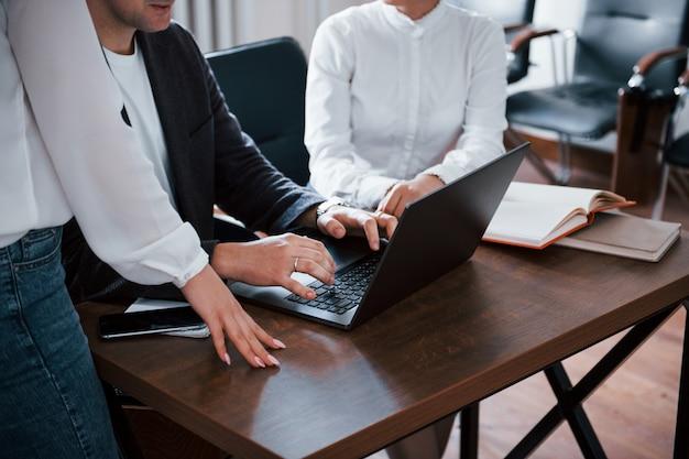 Foto ritagliata. uomini d'affari e manager che lavorano al loro nuovo progetto in classe
