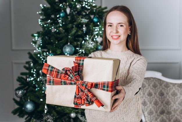 Foto ritratto della ragazza che dà il contenitore di regalo con il nastro rosso