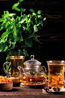 Foto scura di tisana calda con l'olivello spinoso e la menta