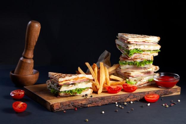 Foto sessione nuovo menu di coffee house, sandwich club fresco con pollo e verdure, insalata di lattuga, patatine fritte e ketchup su legno