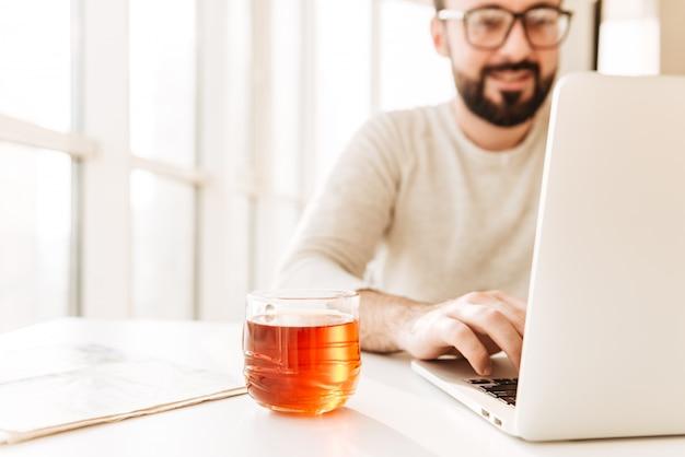 Foto sfocata di uomo caucasico con barba e baffi con notebook, mentre seduto al tavolo con un bicchiere di tè a fuoco al coperto