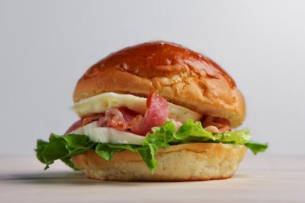 Foto soft focus di hamburger con mozzarella, pancetta e uovo fritto.