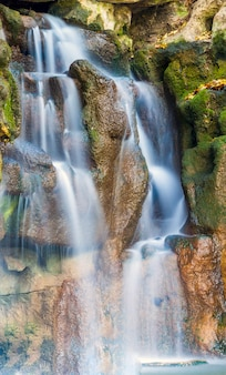 Foto verticale di bella cascata nel parco con muschio verde sulle rocce di pietra bagnate