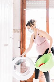 Foto verticale di una donna incinta che indossa una maschera in faccia mentre sta facendo un bucato