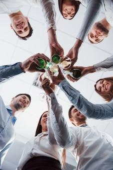 Foto verticale. vista dal basso bussare gli occhiali in ufficio. festeggiamo il successo