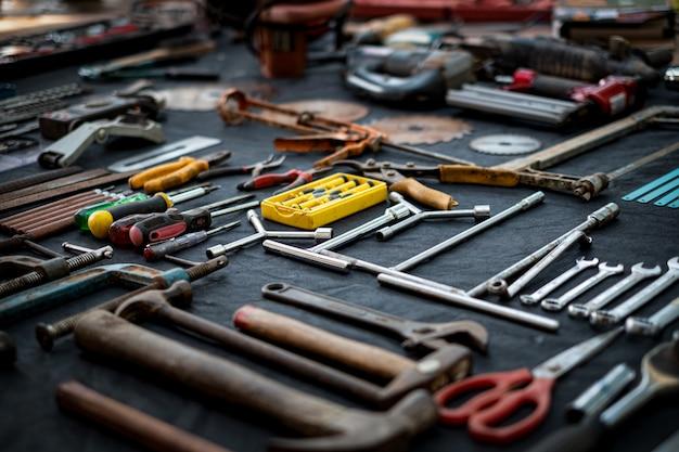 Foto vista dall'alto di una vasta collezione di attrezzi manuali e utensili elettrici molti per il legno su superficie nera isolata