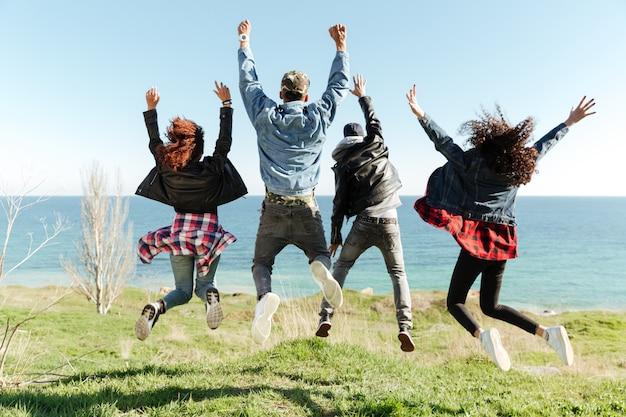 Foto vista posteriore di un gruppo di amici che saltano