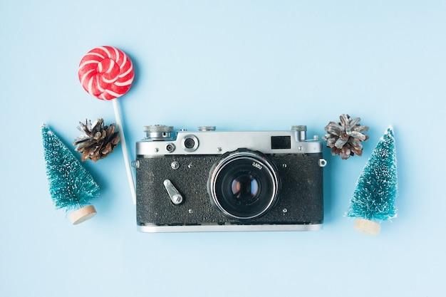 Fotocamera a pellicola retrò, abeti, caramelle e coni. concetto di natale