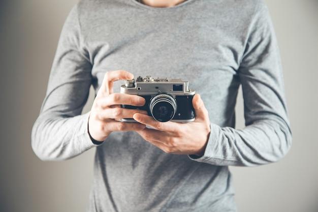 Fotocamera della holding della mano del giovane