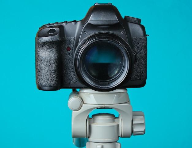Fotocamera digitale moderna con un treppiede sul tavolo blu. vista frontale