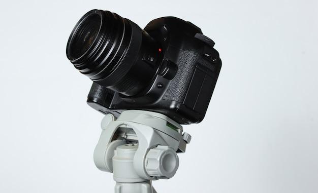 Fotocamera digitale moderna con un treppiede sul tavolo grigio. astrofotografia