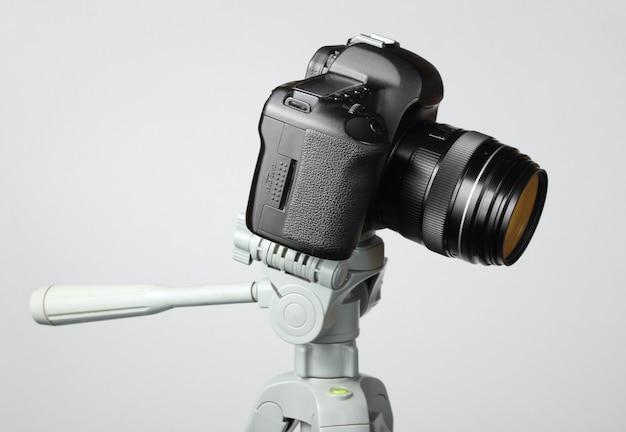 Fotocamera digitale moderna con un treppiede sul tavolo grigio
