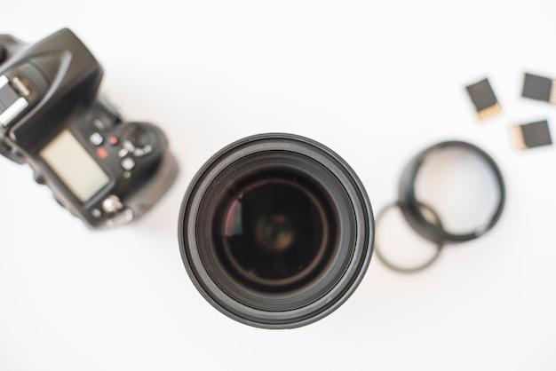 Fotocamera digitale professionale dslr; lenti della macchina fotografica; anelli di prolunga e schede di memoria su sfondo bianco
