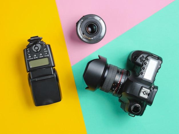 Fotocamera, flash, obiettivo su una superficie pastello.