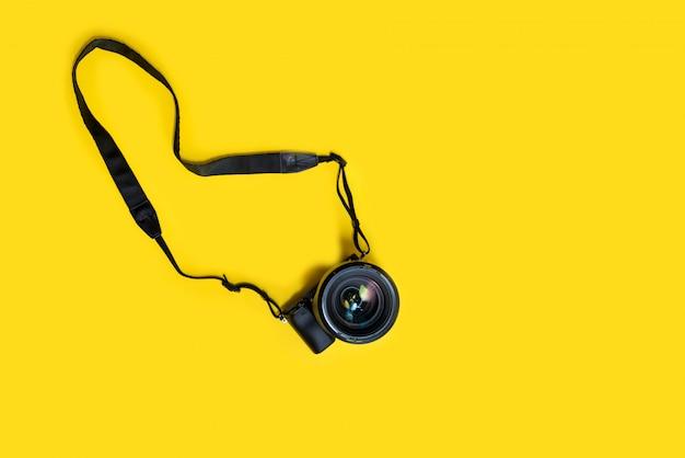 Fotocamera nera mirrorless su sfondo giallo, estate memmories photograher
