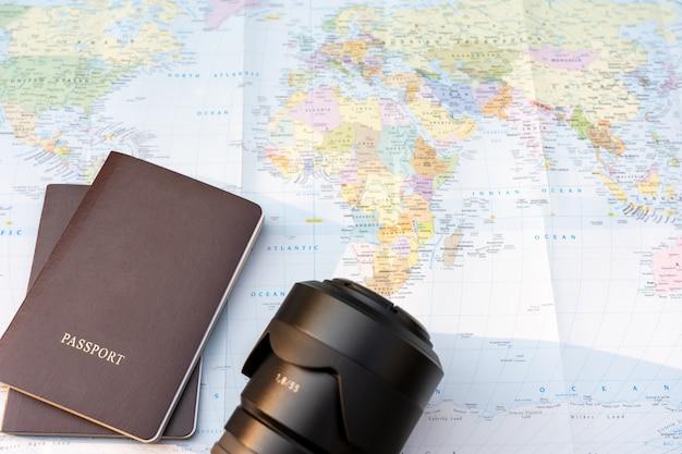 Fotocamera per passaporto e obiettivo su una mappa del mondo. mappa del globo su uno sfondo.