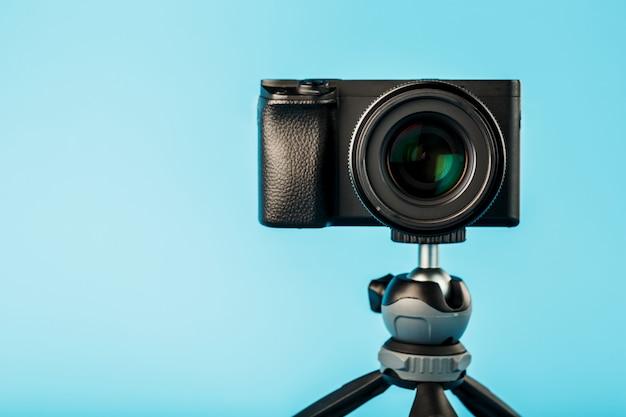 Fotocamera professionale su un treppiede, su sfondo blu. registra video e foto per il tuo blog o rapporto.