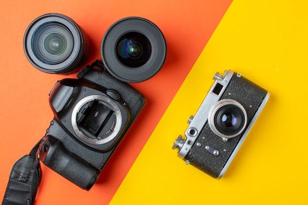 Fotocamera reflex digitale e pellicola con una serie di obiettivi su un tavolo colorato, i progressi delle attrezzature fotografiche