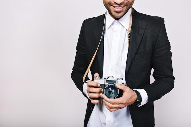 Fotocamera retrò nelle mani del bel ragazzo in tuta. tempo libero, viaggi, giornalista, fotografia, hobby, sorridere, divertirsi.
