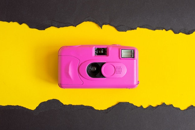 Fotocamera rosa su sfondo colorato. estate ancora in vita. minimo
