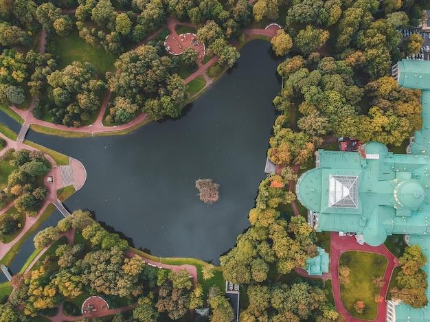Fotografia aerea di un parco con un lago e un palazzo sulla riva, san pietroburgo, russia.