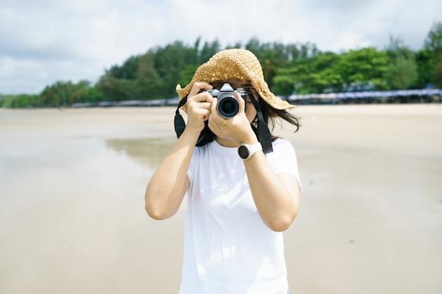 Fotografia della giovane donna del ritratto che porta un cappello usando la sua macchina fotografica mirrorless che copre il suo fronte