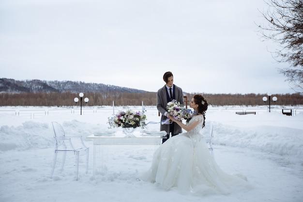 Fotografia di matrimonio in scena in inverno. sposi con un bellissimo bouquet accanto a un tavolo di vetro e sedie