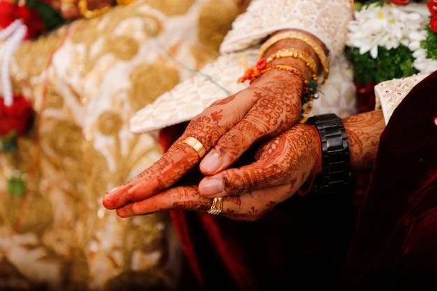 Fotografia di matrimonio indiano, mani dello sposo e della sposa