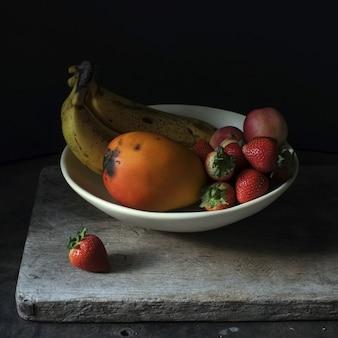Fotografia di natura morta della frutta fresca in un piatto bianco su fondo nero
