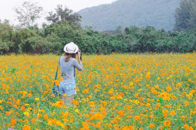 Fotografia femminile con fotocamera scattare una foto di fiori
