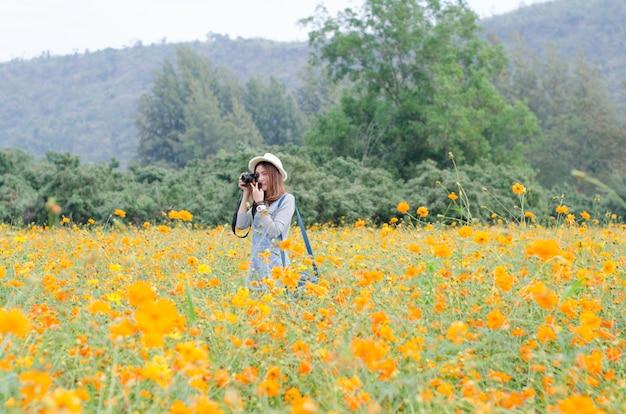 Fotografia femminile con la macchina fotografica che cattura un'immagine del fiore del tagete