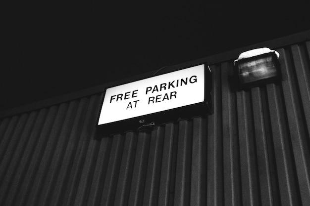 Fotografia in scala di grigi del parcheggio gratuito al cartello posteriore