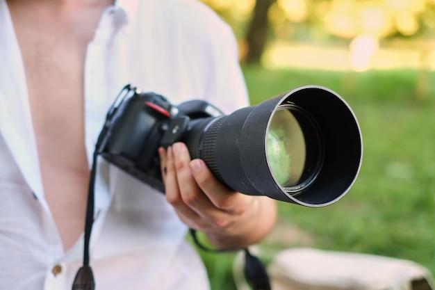 Fotografia o concetto di viaggiatore. il fotografo tiene la fotocamera dsrl nelle sue mani