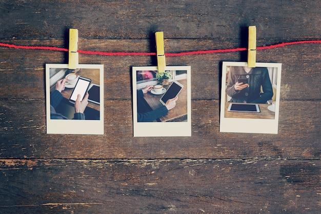 Fotografie di foto donna utilizzando il telefono appeso sul clothesline e sullo sfondo di legno. annata filtrata.