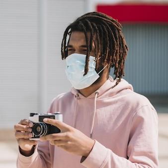 Fotografo afroamericano che indossa una maschera medica