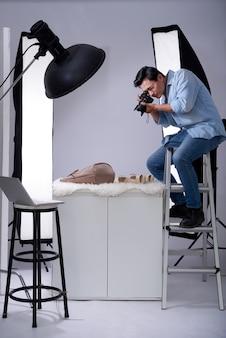 Fotografo asiatico che si siede sulla scala in studio con la macchina fotografica e che prende le foto degli oggetti di modo