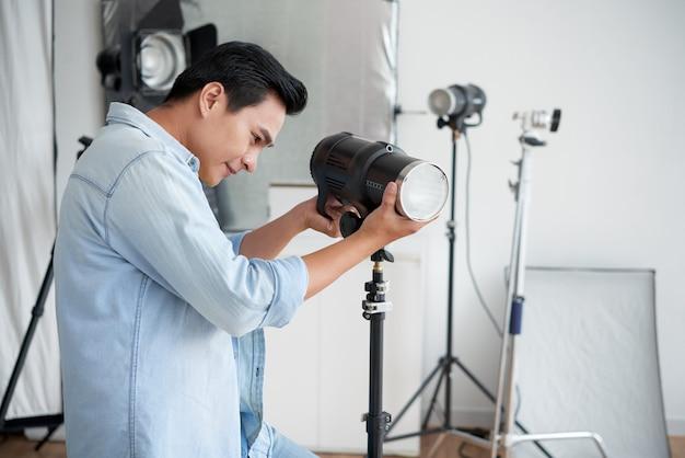 Fotografo asiatico sorridente che regola lampada di illuminazione in studio professionale