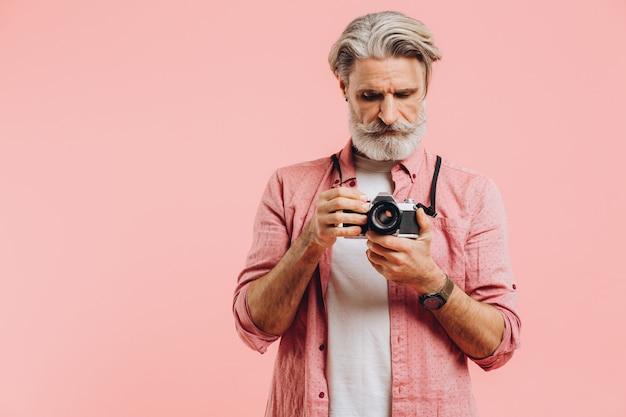 Fotografo barbuto di mezza età che tiene una macchina fotografica sul rosa.