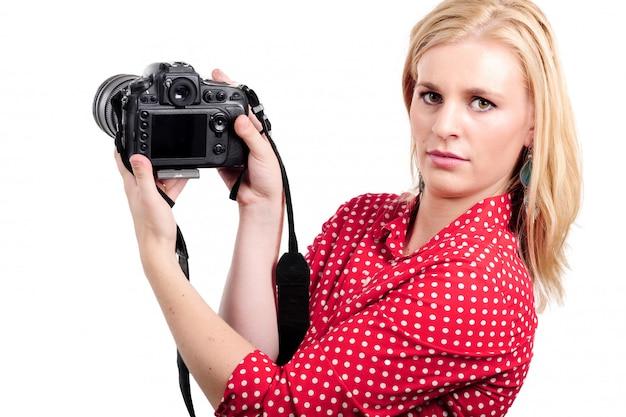 Fotografo biondo grazioso della donna con la sua macchina fotografica, su bianco