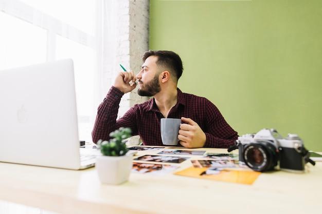 Fotografo che beve caffè mentre sul lavoro
