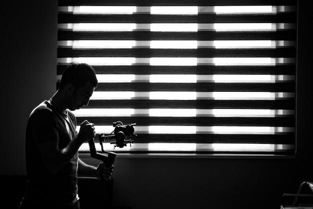 Fotografo che controlla la sua macchina fotografica nell'oscurità.