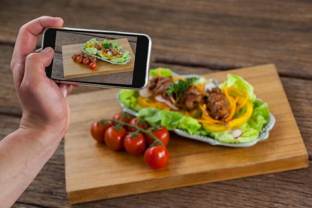 Fotografo che fa clic su un'immagine del cibo tramite smartphone