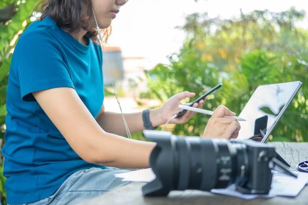 Fotografo che si siede e modifica le foto utilizzando un tablet. dimensioni portatili, funzionalità intelligenti
