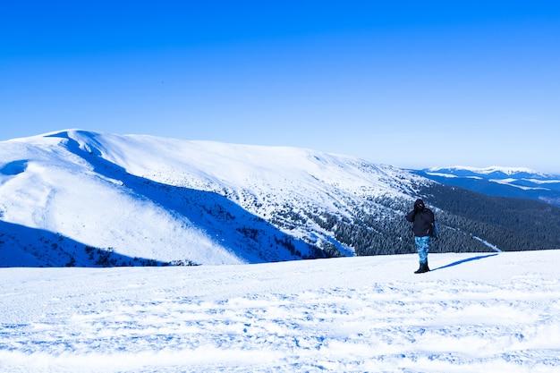 Fotografo che sta con la macchina fotografica sulla collina con la vista panoramica della valle di inverno